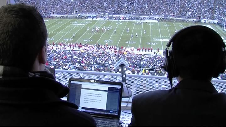 Students sit in the press box doing live radio coverage of a Penn State football game