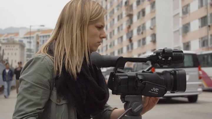 A Penn State journalism student sets up a video camera on the streets of Hong Kong