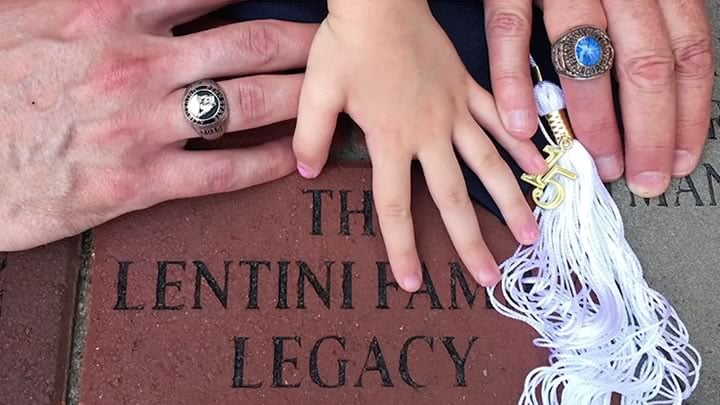 The Lentini family place their hands over a donated legacy brick