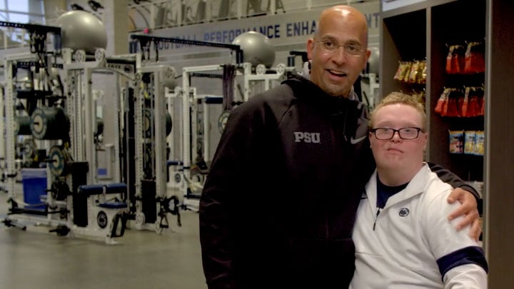 Penn State football coach James Franklink hugs program participant, Zach Williams