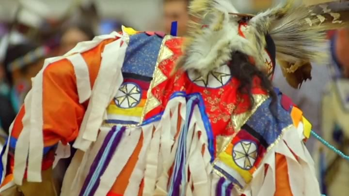 Dancer in ornate clothing and beads dances at a traditional American Indian Powwow